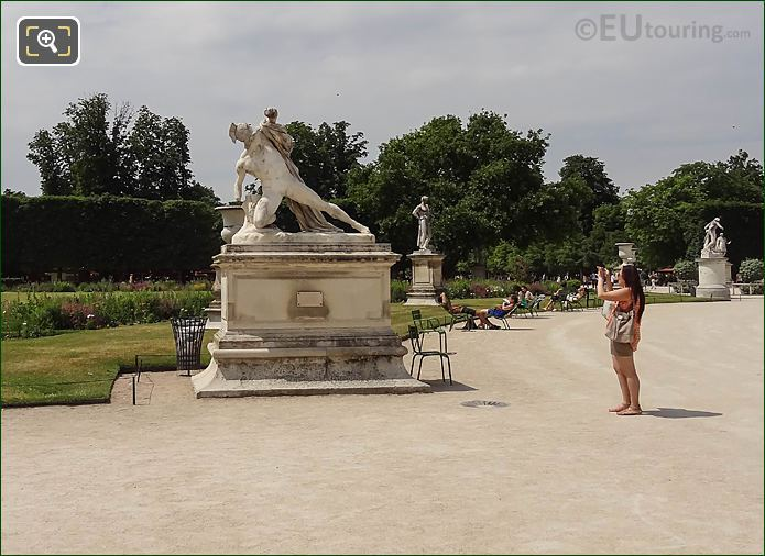 Tourist Taking Pictures Of Statue In Tuileries Gardens